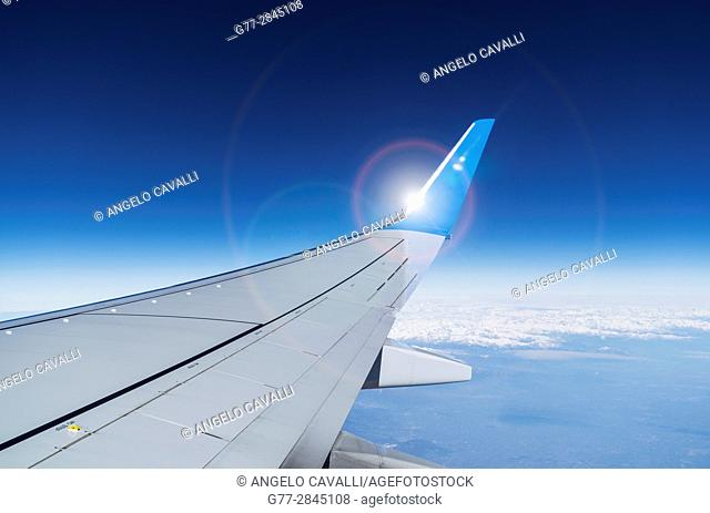 Airplane wing in a deep blue sky