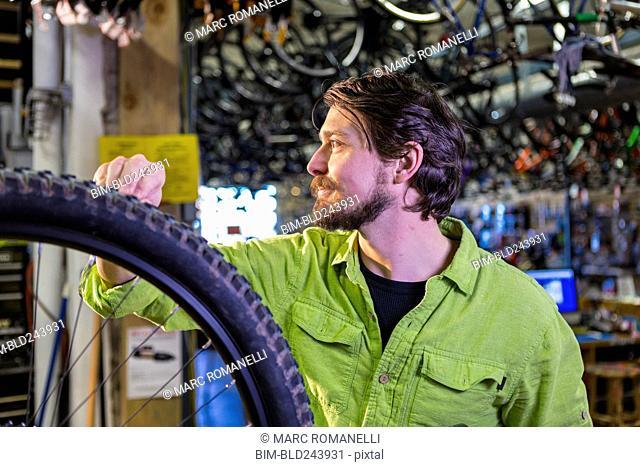 Caucasian worker repairing bicycle wheel in shop