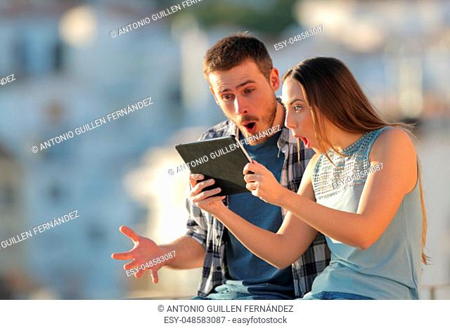 Amazed friends finding online content on a tablet outdoors in a town at sunset