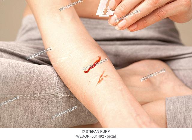 Autoaggressive young woman scratching herself with razor blade