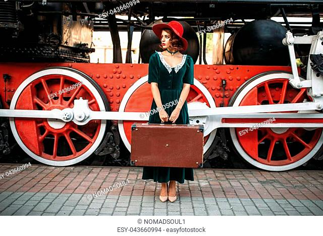 Woman in red hat with suitcase in hands against vintage steam locomotive, red wheels closeup. Old train. Railway engine, railroad journey