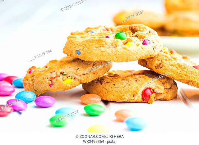 Sweet cookies with colorful candies on white table