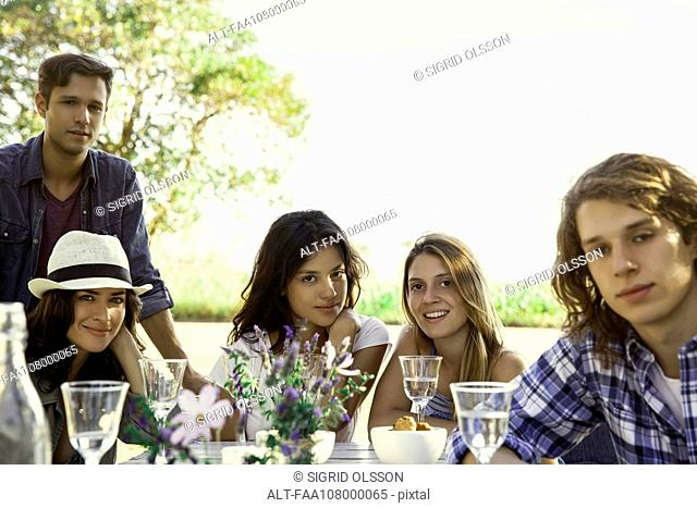Friends enjoying meal together outdoors, portrait