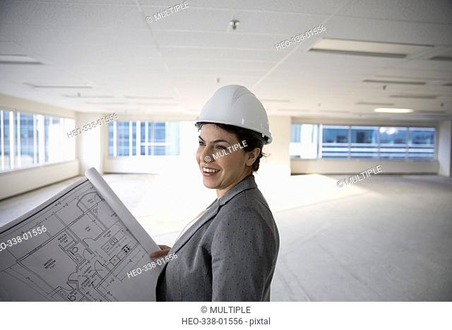 Smiling female architect reviewing blueprints in empty, unfinished open plan highrise office