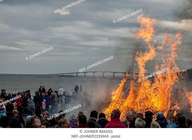 People watching large campfire on beach
