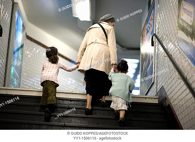 Paris, France. Grandmother climbing the stairs of a down town subway station with her two grandchildren, on their way to the underground's exit