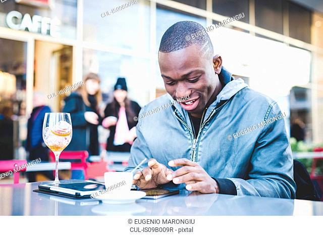Young man sitting outside cafe, using smartphone, smiling