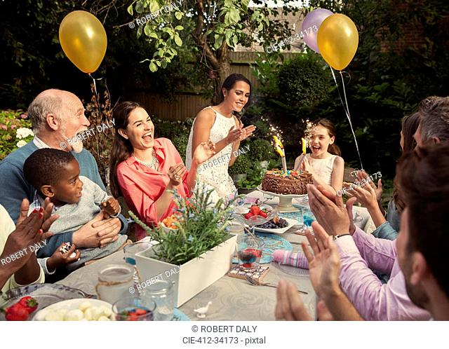 Multi-ethnic multi-generation family clapping celebrating birthday with fireworks cake at patio table