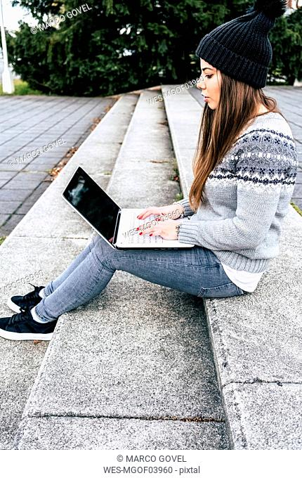 Young woman sitting outdoors on stairs using laptop