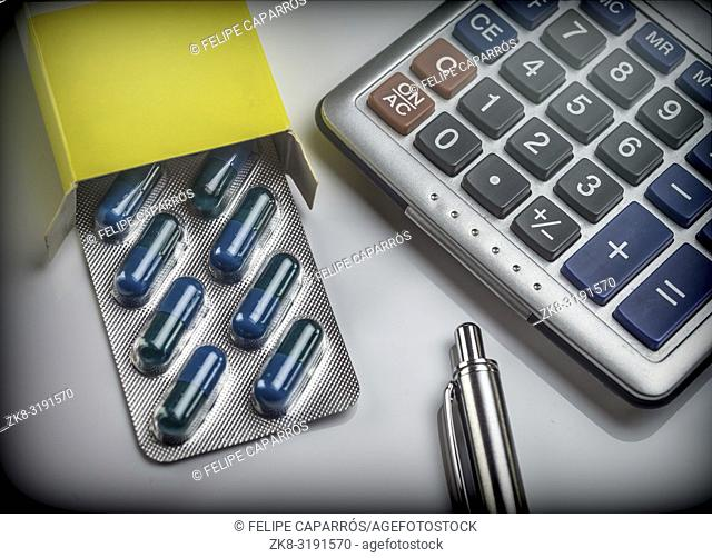 Blister pack of pills next to a calculator, concept of copayment health