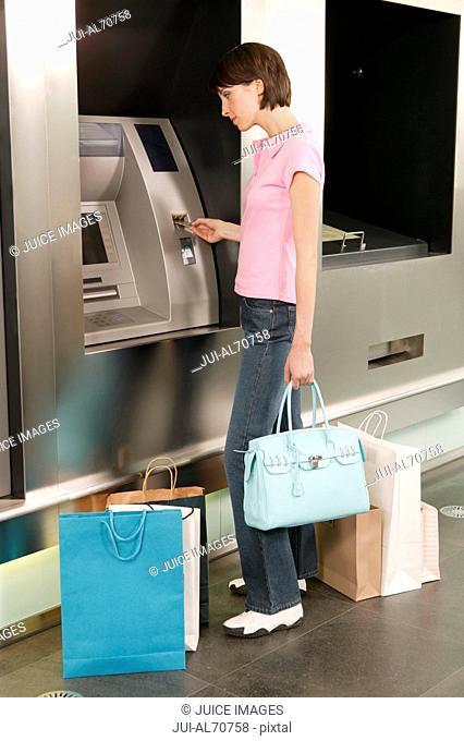 Female shopper using an automated banking machine
