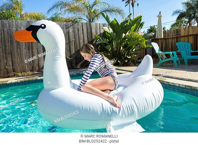 Caucasian girl sitting on inflatable swan in swimming pool