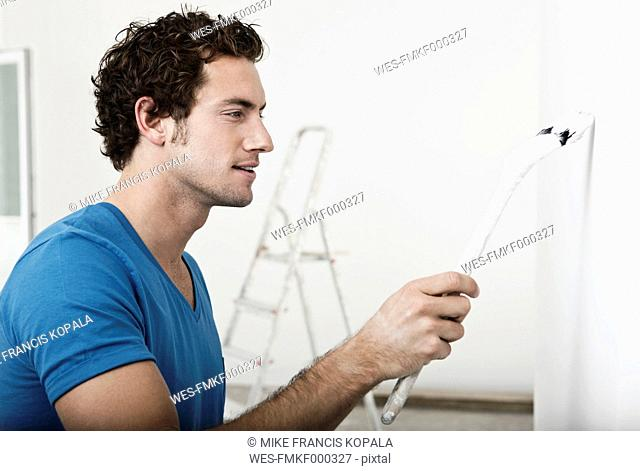 Germany, Cologne, Close up of young man painting in renovating apartment