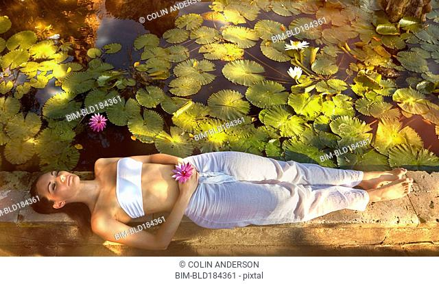Pacific Islander woman laying in garden