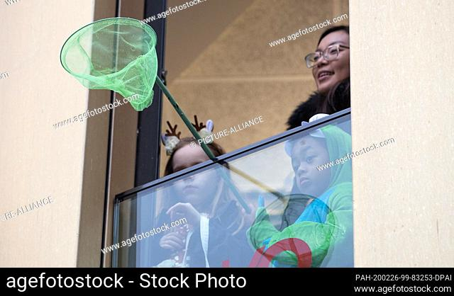 22 February 2020, Lower Saxony, Osnabrück: A young carnivalist stands at a window with a catching device waiting for camels at the traditional carnival...