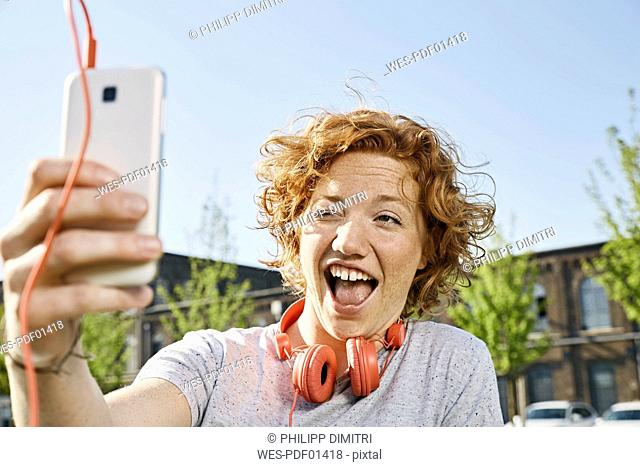 Playful young woman with headphones taking a selfie in urban surrounding