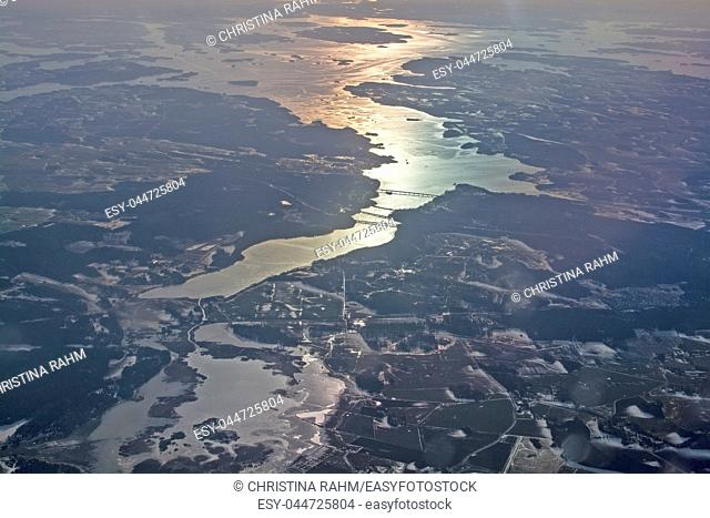 Aerial landscape with golden light over water and forest in Sweden