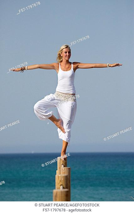 Healthy young woman balancing on a wooden post