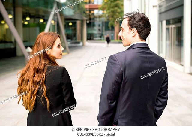 Rear view of businesspeople in city face to face smiling