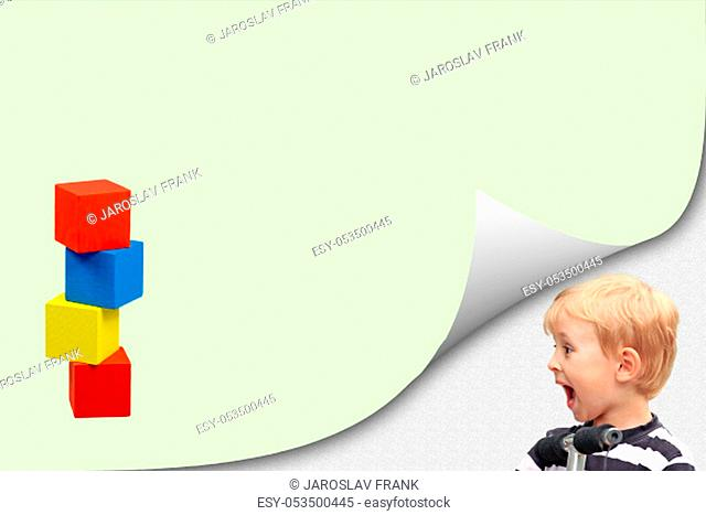 Surprised blond boy is standing in an exposed corner next to a blank yellow page with a tower of colorful wooden cubes ready for your text