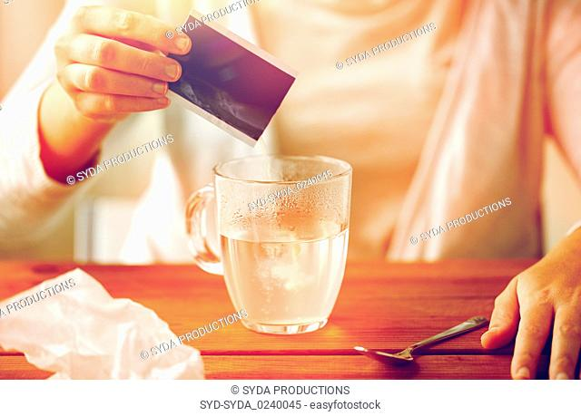 woman pouring medication into cup of water