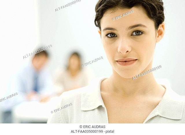 Young professional woman looking at camera, portrait, colleagues in background