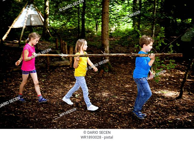 Children carrying wood in a forest camp, Munich, Bavaria, Germany