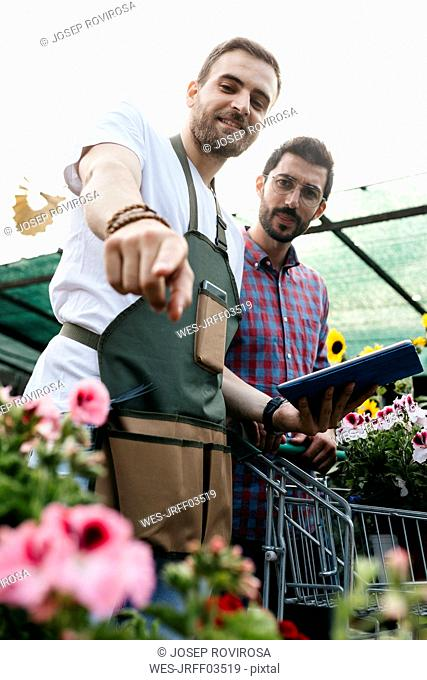 Worker with tablet in a garden center advising customer