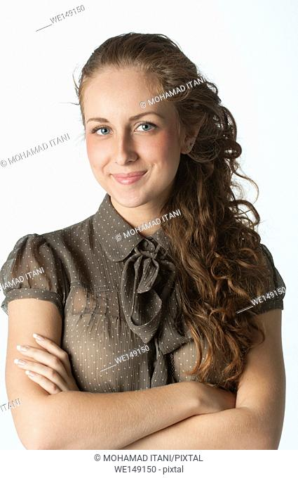 Beautiful young Caucasian woman arms folded smiling against a white background