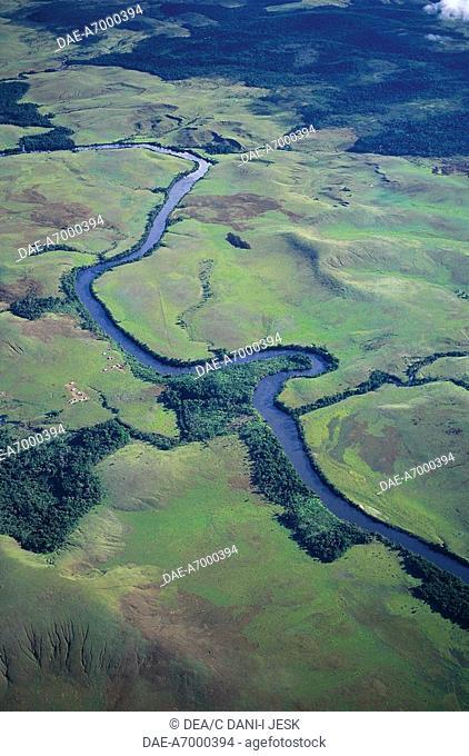 Venezuela - Bolivar State - Canaima National Park (Parque Nacional Canaima, UNESCO World Heritage List, 1994). Aerial view of a river flowing across La Gran...