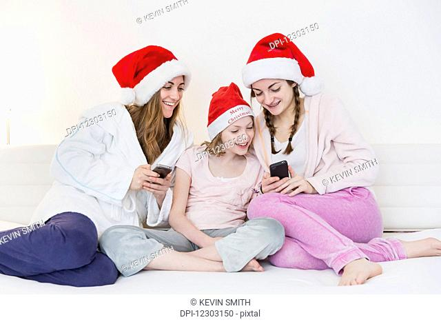 Three sisters wearing santa hats, pajamas and robes and sitting together on a couch looking at two cell phones while smiling; Bonn, Nordrhein Westfalen, Germany