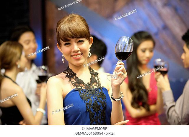 Young woman holding wineglass and smiling at the camera