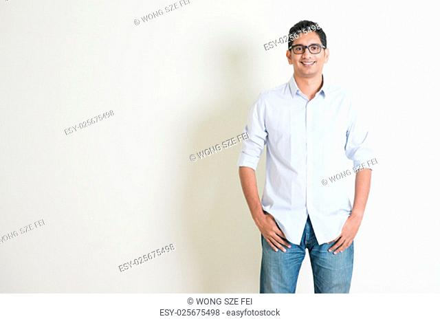 Portrait of handsome casual business Indian guy smiling, hands in pocket, standing on plain background with shadow, copy space at side