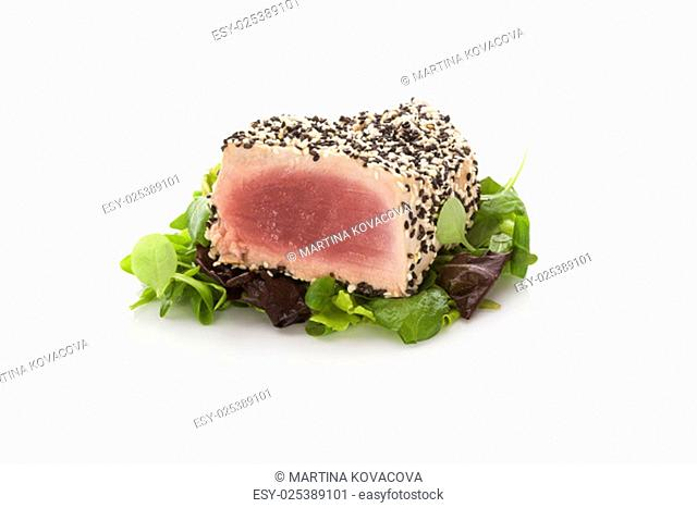 Delicious tuna steak on green salad isolated on white background. Culinary seafood eating