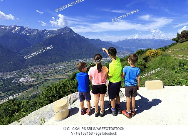 Children look towards Monte Legnone from Alpe Bassetta, Lower Valtellina, Sondrio province, Lombardy, Italy