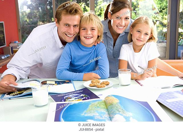 Parents by son and daughter 6-8 with homework, smiling, portrait, world atlas in foreground