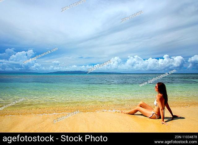 Young woman in bikini sitting on the beach on Taveuni Island, Fiji. Taveuni is the third largest island in Fiji