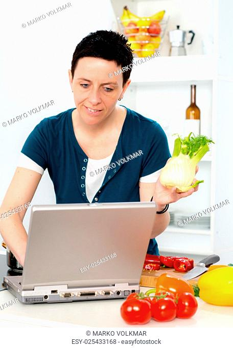 young woman with short dark hair looking for cooking recipe in the internet