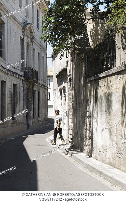 Pedestrian crossing over a brightly lit, narrow, curving street in the old quarter of Avignon, Provence, France