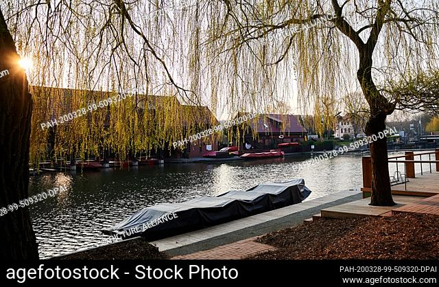 28 March 2020, Brandenburg, Lübben: In Lübben many canoes and boats lie covered on the edge or in the boathouse. Before the Corona crisis many tourists could...
