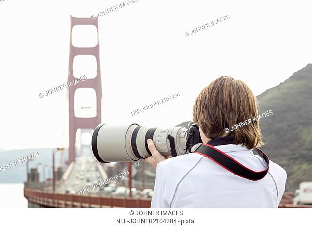 Boy taking picture, Golden Gate Bridge on background