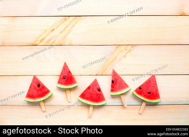 Watermelon slice popsicles on white wooden background. Copy space