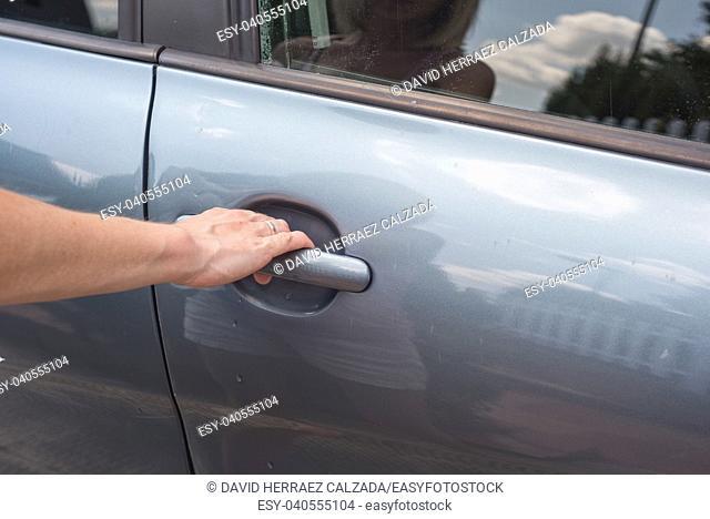Woman hand opening car door close up