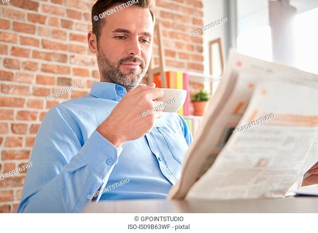 Man reading newspaper drinking coffee