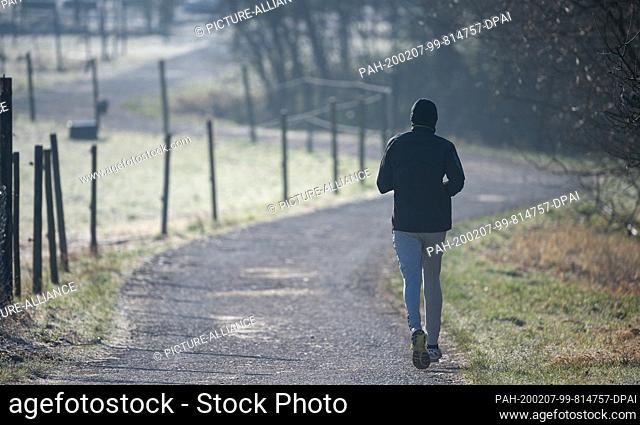 07 February 2020, Baden-Wuerttemberg, Winterbach: A man jogging across a dirt road in the morning. Photo: Sebastian Gollnow/dpa