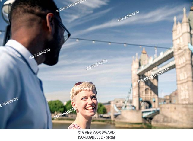 Young couple walking outdoors, smiling, Tower Bridge in background, London, England, UK