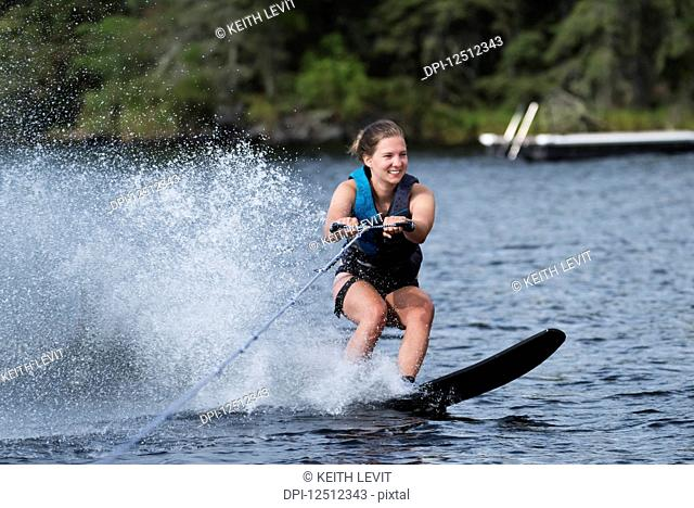 A young woman wakeboarding behind a boat on a lake; Lake of the Woods, Ontario, Canada