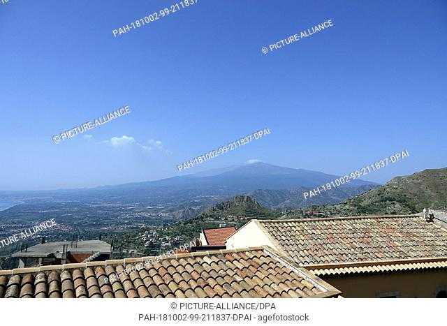 06 September 2018, Italy, Castelmola: 06 September 2018, Italy, Castelmola: View over the roofs of the mountain village Castelmola to the volcano Etna