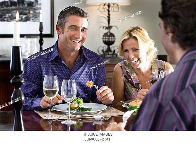 Group of friends having lunch with glasses of wine at table, smiling