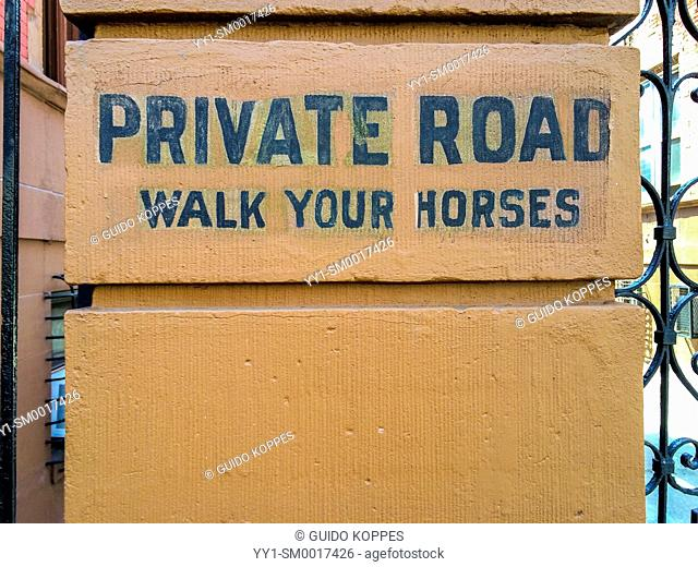 Harlem, New York City, USA. 'Private Road'' sign besides an entrance to a private road in between blocks of houses